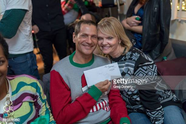 Thomas and Lisa Collabro display their Secret Santa Gifts at The Bay Ugly Sweater And Secret Santa Christmas Party at Private Residence on December...
