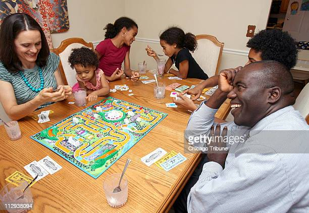 Thomas Appiah and wife Katrina left enjoy fruit smoothies as they play the board game Life with their family at their Schaumburg home in Illinois on...