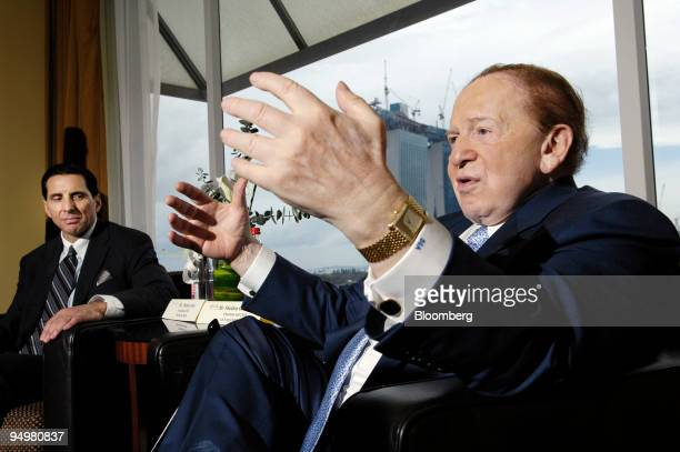 Thomas Arasi president and chief executive officer of Las Vegas Sands Corp's Marina Bay Sands resort left looks on as Sheldon Adelson chairman and...