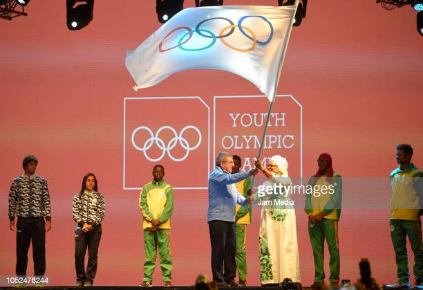 Thomas Bach Presidente of IOC transfers the Olympic flag to representative of Senegal on day 12 during the closing ceremony of Buenos Aires 2018...