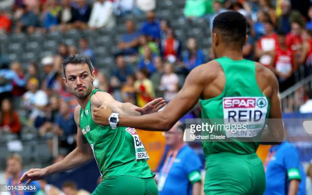 Thomas Barr of Ireland receives the baton from Leon Reid of Ireland as they compete in the Men's 4 x 400m Relay Round 1 Heat 2 during day four of the...