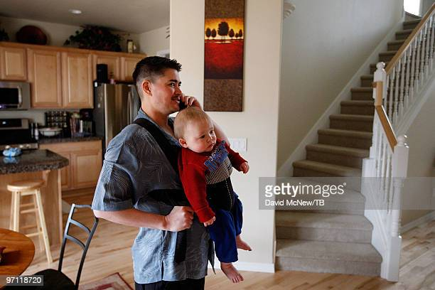 Thomas Beatie talks on the phone while holding his son Austin Alexander Beatie on February 17 2010 in Bend Oregon Thomas a transgender male is 17...