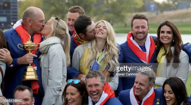 Thomas Bjorn of Denmark and captain of the European Team holds the Ryder Cup with his partner Grace Barber as Jon Rahm embraces his girlfriend Kelley...