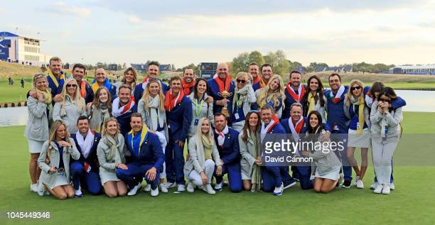Thomas Bjorn of Denmark and captain of the European Team raises the Ryder Cup with his team and their wives and partners after their 17.5-10.5 win...