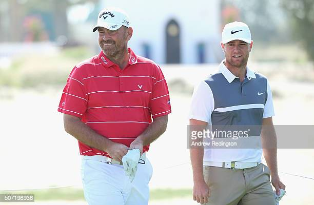 Thomas Bjorn of Denmark and Lucas Bjerregaard of Denmark share a joke on the eighth hole during the second round of the Commercial Bank Qatar Masters...