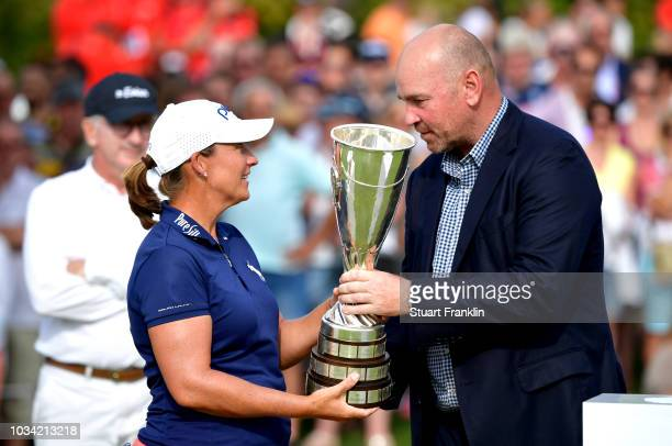Thomas Bjorn Ryder cup captain hands the Evian Championship Trophy over to winner Angela Stanford of the United States during Day Four of The Evian...