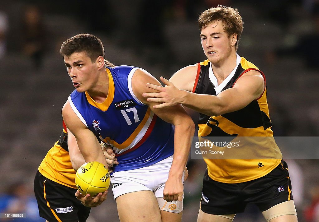 Thomas Boyd of the Ranges handballs whilst being tackled by Daylan Kempster of the Stingrays during the TAC Cup final match between Eastern Ranges and the Dandenong Southern Stingrays at Etihad Stadium on September 22, 2013 in Melbourne, Australia.