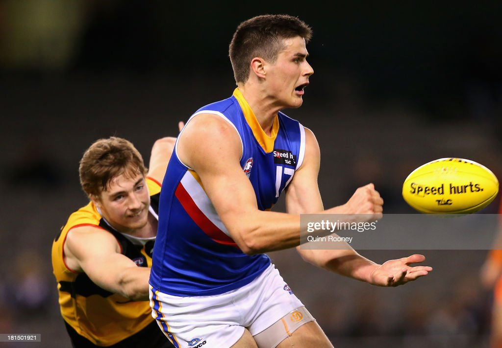 Thomas Boyd of the Ranges handballs whilst being tackled during the TAC Cup final match between Eastern Ranges and the Dandenong Southern Stingrays at Etihad Stadium on September 22, 2013 in Melbourne, Australia.