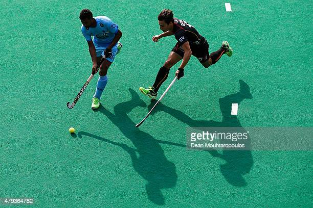 Thomas Briels of Belgium and Lakra Birendra of India battle for the ball during the Fintro Hockey World League SemiFinal match between India and...