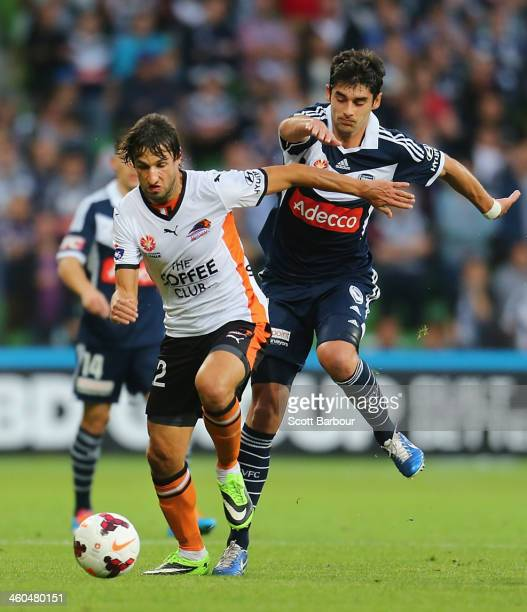 Thomas Broich of the Roar and Guilherme Finkler of the Victory compete for the ball during the round 13 ALeague match between the Melbourne Victory...
