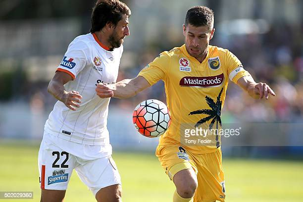 Thomas Broich of the Roar contests the ball with Nick Montgomery of the Mariners during the round 11 ALeague match between the Central Coast Mariners...