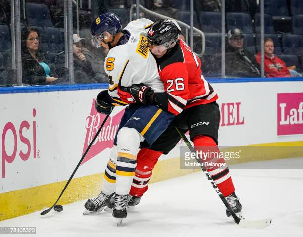 Thomas Caron of the Quebec Remparts and Jordan Lepage of the Shawinigan Cataractes battle for the puck during their QMJHL hockey game at the...