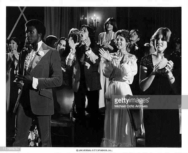 Thomas Carter Tim Matheson Donna Wilkes and Lee Purcell applauding during a party in a scene from the film 'Almost Summer' 1978