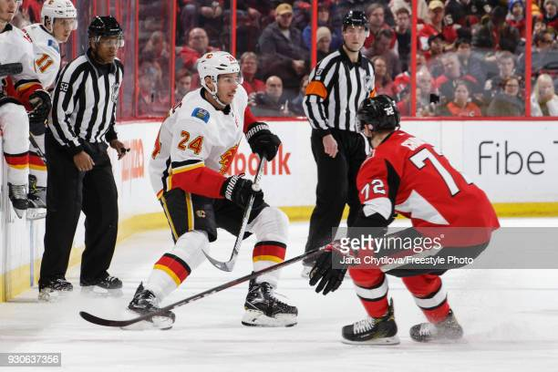 Thomas Chabot of the Ottawa Senators defends against Travis Hamonic of the Calgary Flames at Canadian Tire Centre on March 9 2018 in Ottawa Ontario...