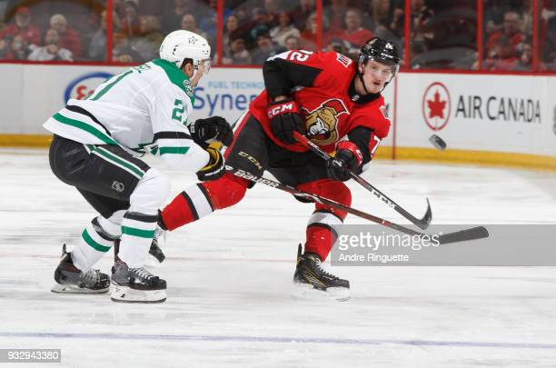 Thomas Chabot of the Ottawa Senators shoots the puck against Antoine Roussel of the Dallas Stars at Canadian Tire Centre on March 16 2018 in Ottawa...