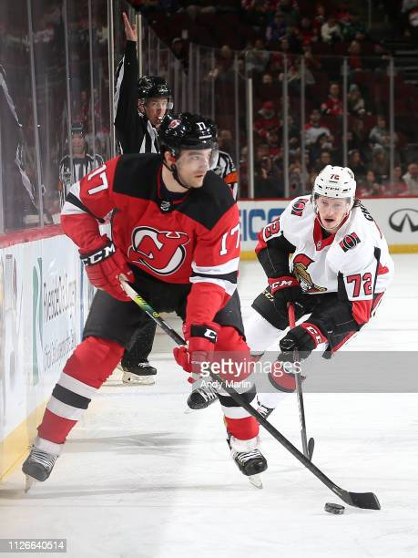 Thomas Chabot of the Ottawa Senators skates after Kenny Agostino of the New Jersey Devils as he controls the puck during the first period at the...