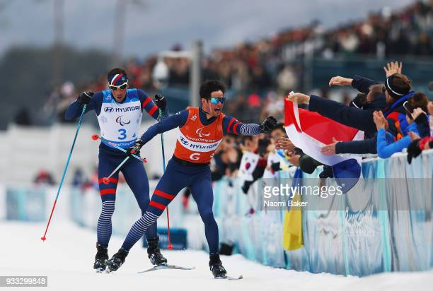 Thomas Clarion and his guide Antoine Bollet of France collect a flag before crossing the finish line to win the Gold medal for the 4x25km Open relay...