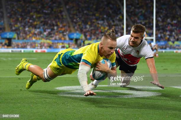 Thomas Connor of Australia dives over for a try under pressure from Tom Mitchell of England during the Rugby Sevens Men's Pool B match between...