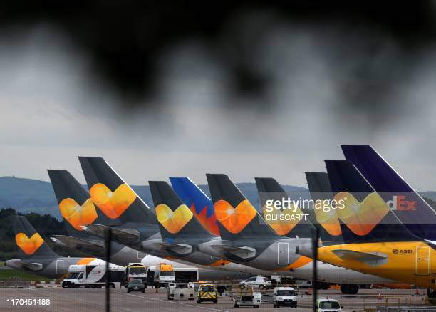 TOPSHOT Thomas Cook logos are pictured on the tailfins of the company's passenger aircraft parked on tarmac at Manchester Airport in Manchester...