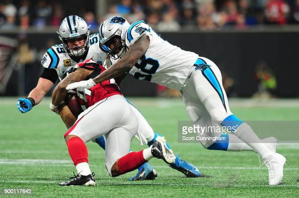 Thomas Davis and Luke Kuechly of the Carolina Panthers tackle Devonta Freeman of the Atlanta Falcons during the first half at MercedesBenz Stadium on...