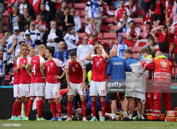Thomas Delaney, Andreas Christensen and Jonas Wind of Denmark look dejected as Christian Eriksen of Denmark receives medical treatment during the...