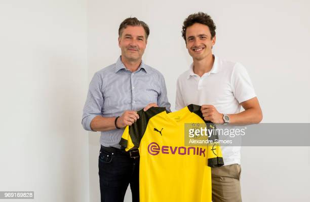 Thomas Delaney holds up the Borussia Dortmnud shirt with Michael Zorc as he signs for the club on June 7 2018 in Dortmund Germany