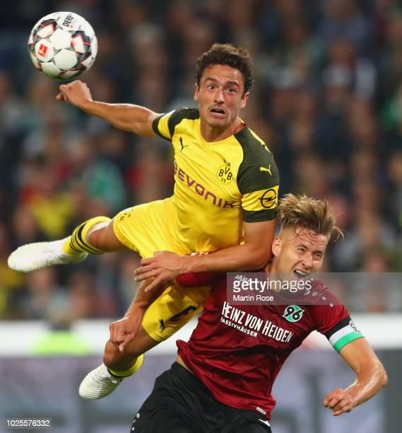 Thomas Delaney of Borussia Dortmund jumps over Waldemar Anton of Hannover 96 during the Bundesliga match between Hannover 96 and Borussia Dortmund at...