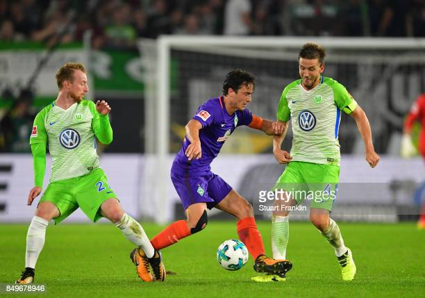Thomas Delaney of Bremen is challenged by Maximilian Arnold and Ignacio Camacho of Wolfsburg during the Bundesliga match between VfL Wolfsburg and SV...
