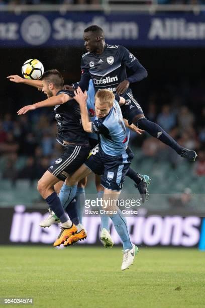 Thomas Deng and Terry Antonis of Melbourne challenge Sydney's Matthew Simon and Deyvison Rogerio da Silva Bobo for a header during the ALeague Semi...