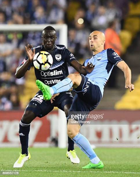 Thomas Deng of the Victory and Adrian Mierzejewski of Sydney FC compete for the ball during the round one ALeague match between the Melbourne Victory...