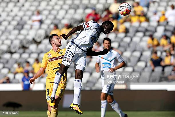 Thomas Deng of the Victory heads the ball ahead of Roy O'Donovan of the Marines during the round 22 ALeague match between the Central Coast Mariners...