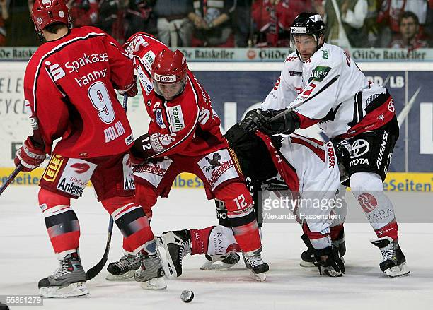 Thomas Dolak and Jason Cipolla of Hanover in action with David McLlwain and Mirko Luedemann of Cologne during the DEL match between Hanover Scorpions...