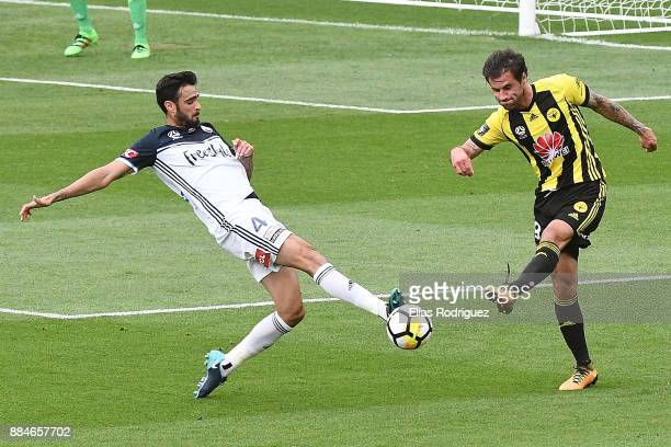 Thomas Doyle of the Wellington Phoenix has his clearance blocked by Rhys Williams of Melbourne Victory during the round nine ALeague match between...