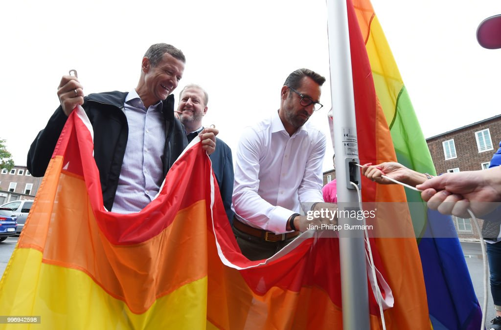 CEO Thomas E. Herrich, CEO Ingo Schiller and CEO Michael Preetz of Hertha BSC raise a rainbow flag in front of the office of Hertha BSC on july 12, 2018 in Berlin, Germany.