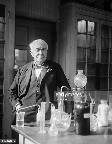 Thomas Edison standing in his lab Edison is standing behind a table that has various beakers and equipment His hand is resting on the table Undated...