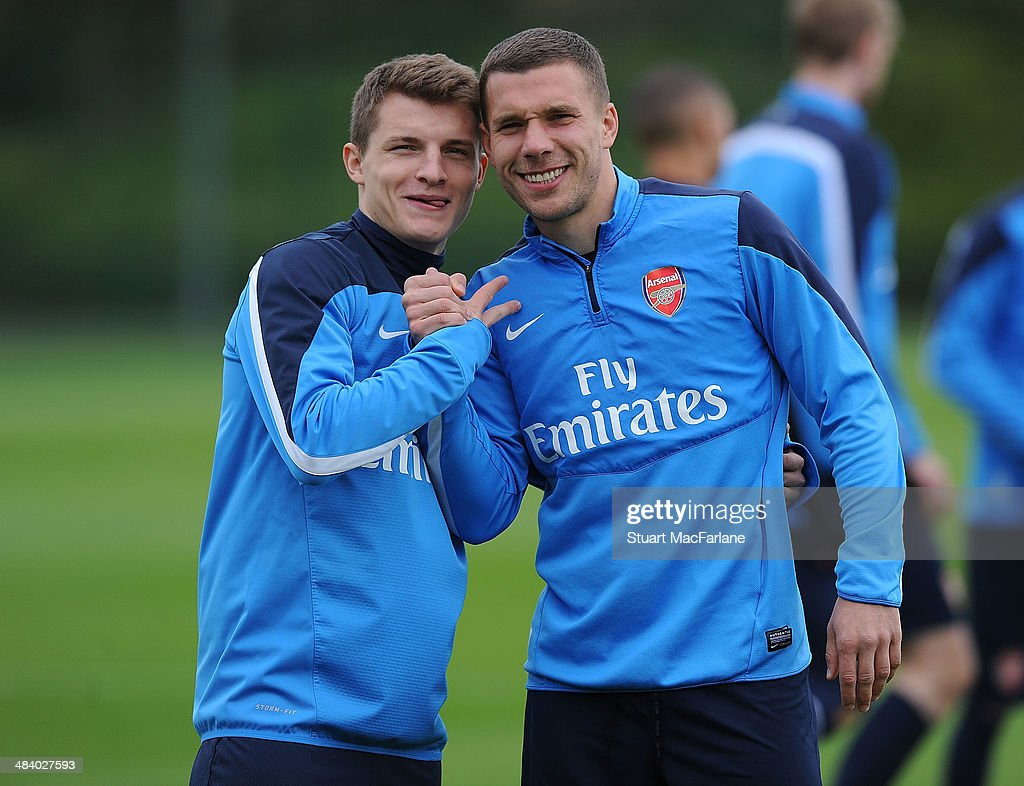 ST. ALBANS, ENGLAND - (L-R) Thomas Eisfeld and Lukas Podolski of Arsenal before a training session at London Colney on April 11, 2014 in St Albans, England.