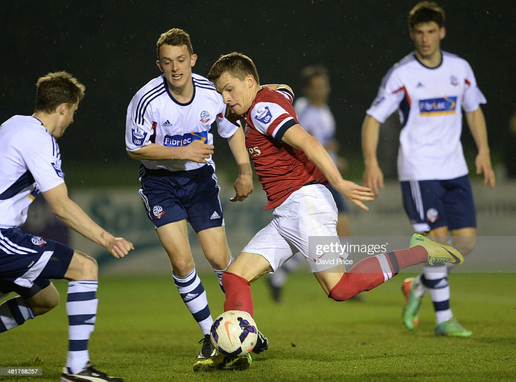 Thomas Eisfeld of Arsenal shoots under pressure from Rob Holding of Bolton during the match between Bolton Wanderers U21 and Arsenal U21 in the Barclays Premier U21 League on March 31, 2014 in Lancaster, England.