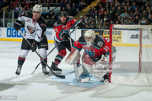 Thomas Foster of the Vancouver Giants is stick checked by Cal Foote as Brodan Salmond of the Kelowna Rockets defends the net during second period on...