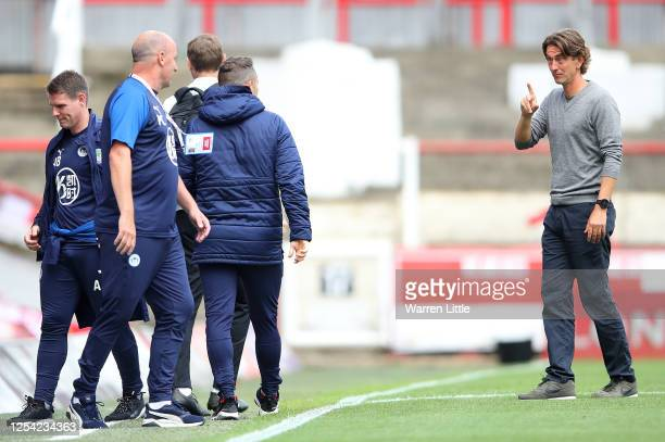 Thomas Frank, manager of Brentford FC speaks with Paul Cook, manager of Wigan Athletic during the Sky Bet Championship match between Brentford and...