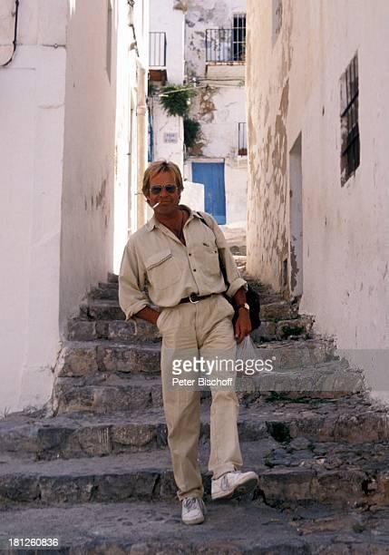 """Thomas Fritsch, neben den Dreharbeiten zur PRO 7 - Serie """"Glueckliche Reise """", Folge 20, """"Ibiza"""", San Carlos/Spanien, , Gasse, Rucksack,..."""