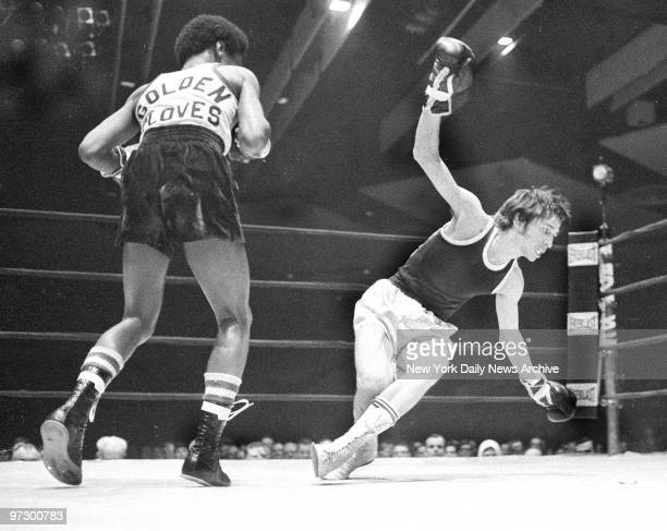 Thomas Glovatto finds his chances of becoming a Golden Gloves champ decreasing as he falls to canvas after taking a pounding from Richard Harris in...