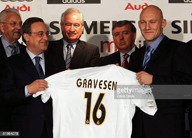 Thomas Gravesen holds up a Real Madrid shirt beside club President Florentino Perez after signing at the Bernabeu on January 14, 2005 in Madrid,...