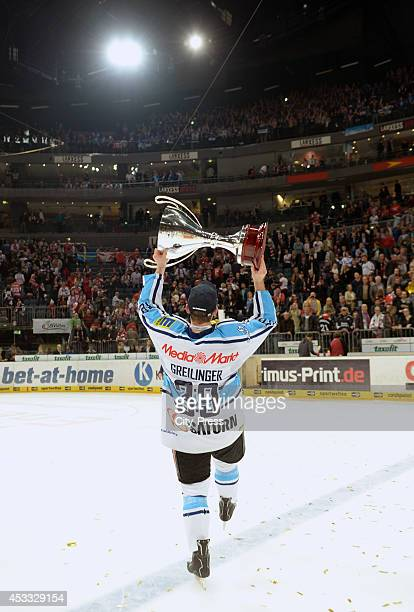 Thomas Greilinger holds the trophy after game seven of the DEL playoff final on April 29, 2014 in Cologne, Germany.