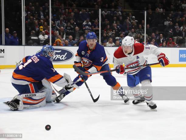 Thomas Greiss and Adam Pelech of the New York Islanders defend against Brendan Gallagher of the Montreal Canadiens during the first period at NYCB...