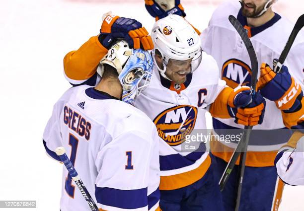 Thomas Greiss and Anders Lee of the New York Islanders celebrate their 4-0 victory against the Philadelphia Flyers in Game Seven of the Eastern...