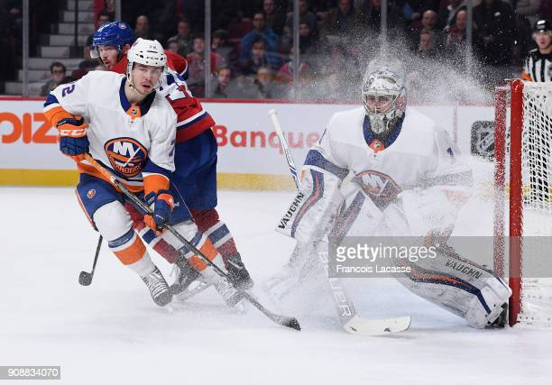 Thomas Greiss and Anthony Beauvillier of the New York Islanders defend the net against Paul Byron of the Montreal Canadiens in the NHL game at the...