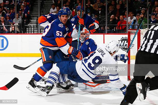 Thomas Greiss and Casey Cizikas of the New York Islanders defend the net against Joffrey Lupul of the Toronto Maple Leafs during the game at the...
