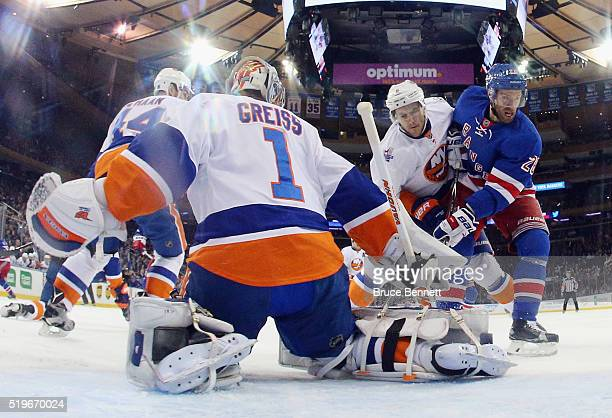 Thomas Greiss and Ryan Pulock of the New York Islanders defend against Dominic Moore of the New York Rangers during the first period at Madison...