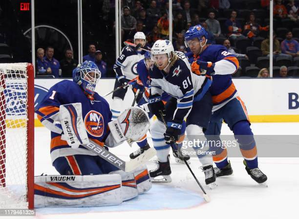 Thomas Greiss and Scott Mayfield of the New York Islanders defend against Kyle Connor of the Winnipeg Jets during the first period at NYCB Live's...