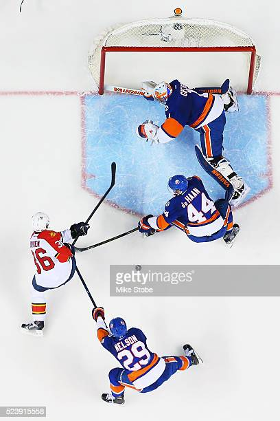 Thomas Greiss, Calvin de Haan and Brock Nelson of the New York Islanders defend the net against Jussi Jokinen of the Florida Panthers in Game Six of...